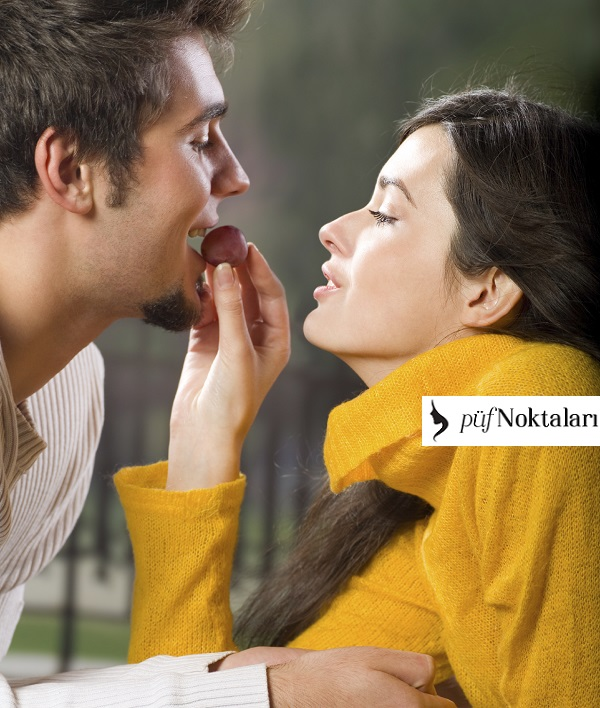 Young amorous couple playfully eating grapes outdoors